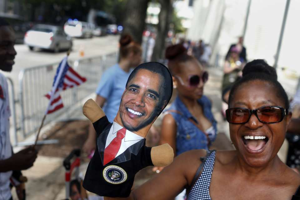 Photo - Ellen Lucas, of Buffalo New York, tries on a puppet of President Barack Obama outside the Charlotte Convention Center during the Democratic National Convention in Charlotte, N.C., on Wednesday, Sept. 5, 2012. (AP Photo/The Tampa Bay Times, Kathleen Flynn) TAMPA OUT; CITRUS COUNTY OUT; PORT CHARLOTTE OUT; BROOKSVILLE HERNANDO OUT; USA TODAY OUT; MAGS OUT ORG XMIT: FLPET112