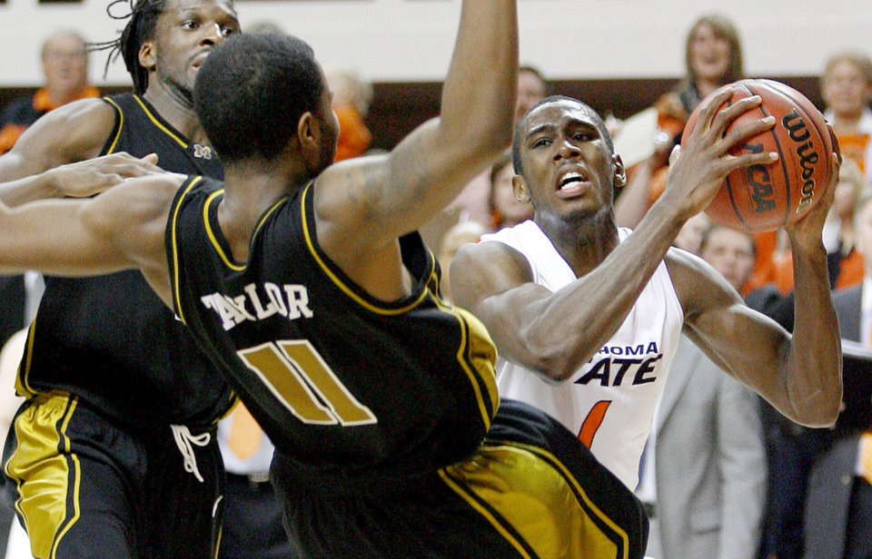 Photo - OSU's Terrel Harris tries to get around Missouri's DeMarre Carroll, left, and Zaire Taylor during the Big 12 college basketball game between Oklahoma State and Missouri at Gallagher-Iba Arena in Stillwater, Okla., Wednesday, Jan. 21, 2009.  PHOTO BY BRYAN TERRY, THE OKLAHOMAN