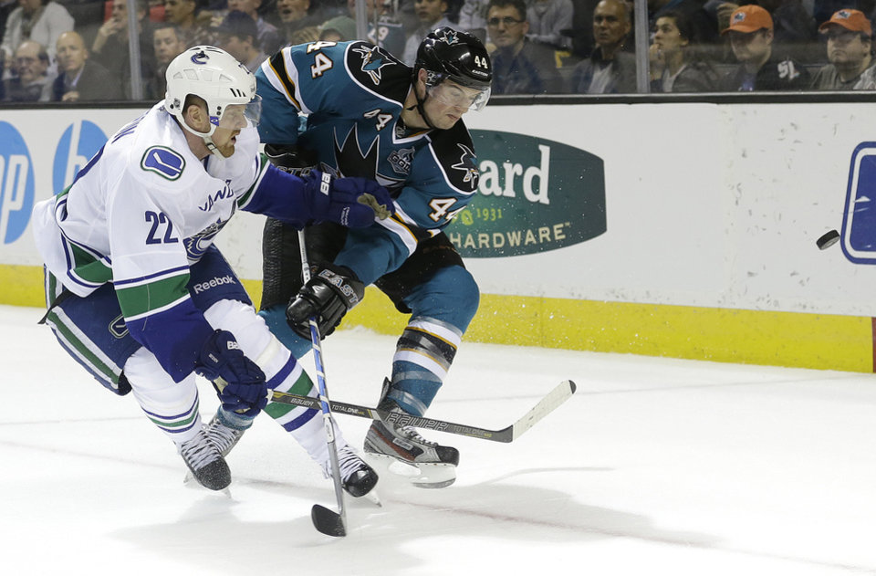 Photo - Vancouver Canucks left wing Daniel Sedin (22), from Sweden, and San Jose Sharks defenseman Marc-Edouard Vlasic (44) fight for the puck during the second period of an NHL hockey game in San Jose, Calif., Monday, April 1, 2013. (AP Photo/Jeff Chiu)