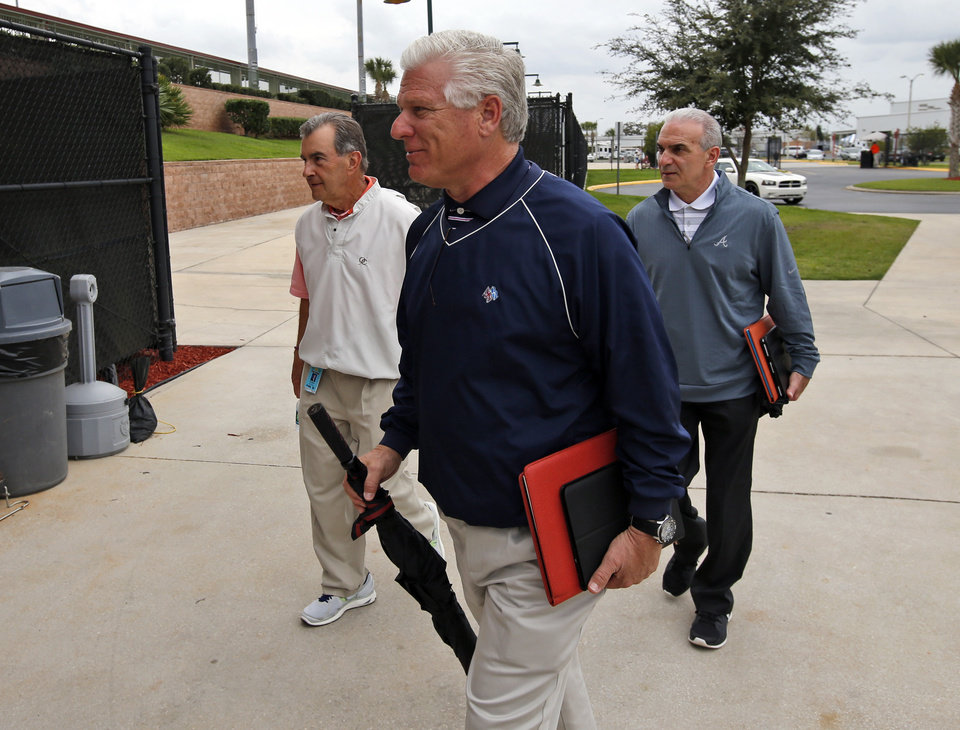 Photo - Frank Wren, center, general manager for the Atlanta Braves, and others arrive for a meeting about the new instant replay rules, at the spring training facility for the Astros, Friday, Feb. 21, 2014, in Kissimmee, Fla. (AP Photo/Alex Brandon)