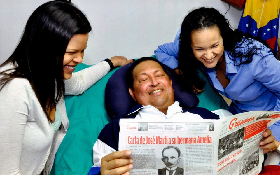 Photo - In this photo released Friday, Feb. 15, 2013 by Miraflores Presidential Press Office, Venezuela's President Hugo Chavez, center, poses for a photo with his daughters, Maria Gabriela, left, and Rosa Virginia as he holds a copy of Cuba's state newspaper Granma at an unknown location in Havana, Cuba, Thursday, Feb. 14, 2013. Chavez remains in Havana undergoing unspecified treatments following his fourth cancer-related operation on Dec. 11. He has hasn't been seen or spoken publicly in more than two months. (AP Photo/Miraflores Presidential Press Office)