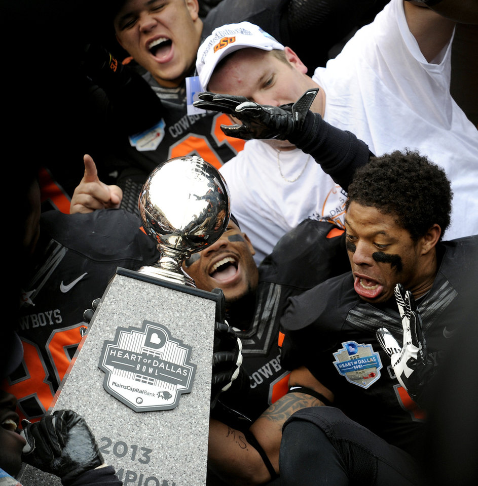 Photo - Oklahoma State players celebrate with the trophy after their 58-14 win over Purdue in the Heart of Dallas Bowl NCAA college football game, Tuesday, Jan. 1, 2013, in Dallas. (AP Photo/Matt Strasen)