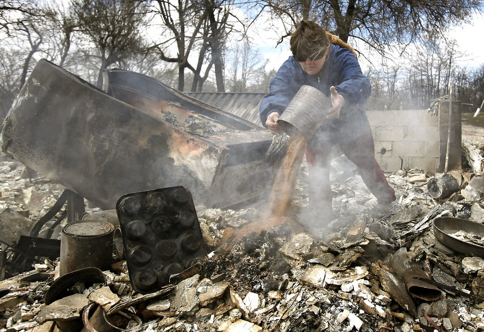 Photo - FIRES / WILDFIRES / HOUSE / DAMAGE/ AFTERMATH / RETURN: Carrie Wertz dumps sand on a smoldering section that remains from her home that was destroyed by wildfires on Friday, April 10, 2009, in Choctaw, Okla.  Photo by Chris Landsberger, The Oklahoman  ORG XMIT: KOD