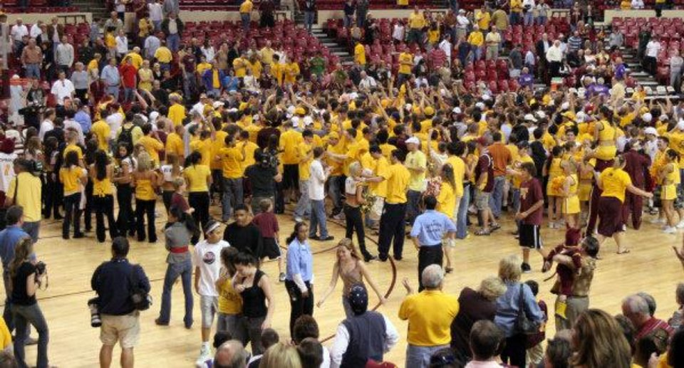 Arizona State fans celebrate on the court following the Sun Devils 68-58 victory over Southern California Sunday, Feb. 18, 2007, in Tempe, Ariz. This was Arizona State's first win in PAC-10 play.(AP Photo/Roy Dabner)
