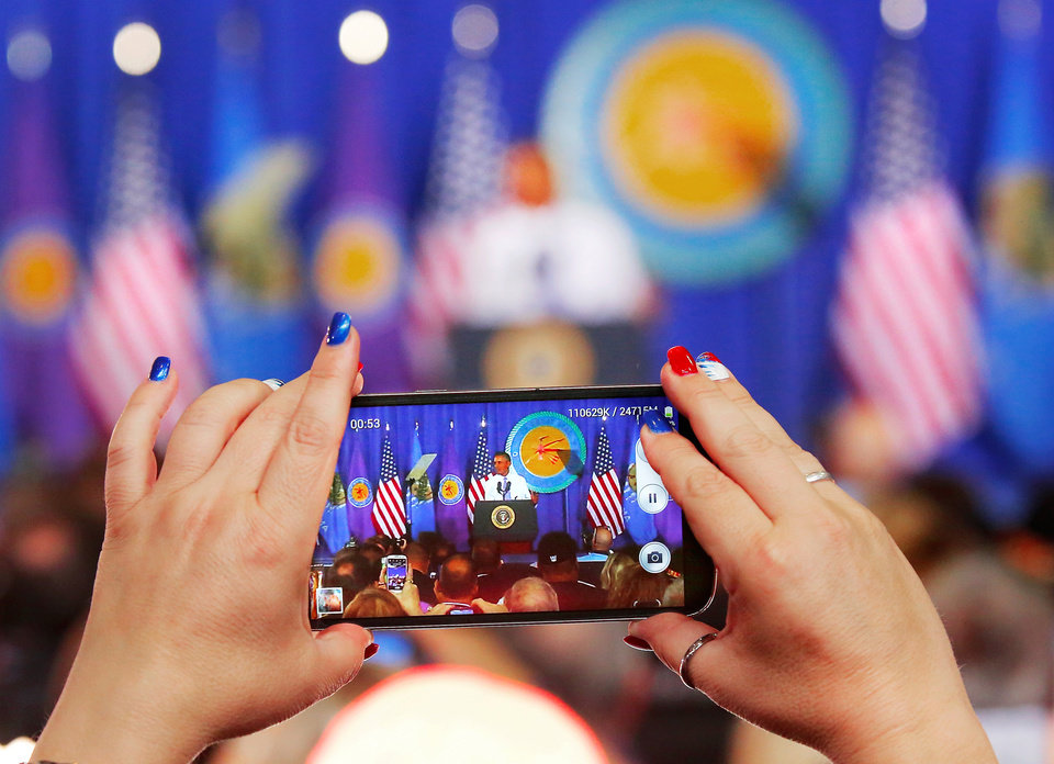 Photo - A woman sporting red, white and blue nails, takes video of  President Barack Obama as he spoke to about 950 people in Durant's new high school on Wednesday, July 15, 2015.  He used his visit in Durant to announce his administration's newest initiative, ConnectHome. It's described as a cooperative effort with communities, the private sector and federal government  to expand high speed broadband to more families across the country. The pilot program is launching in 27 cities and one tribal nation, the Choctaw Nation in southeast Oklahoma. Photo by Jim Beckel, The Oklahoman.