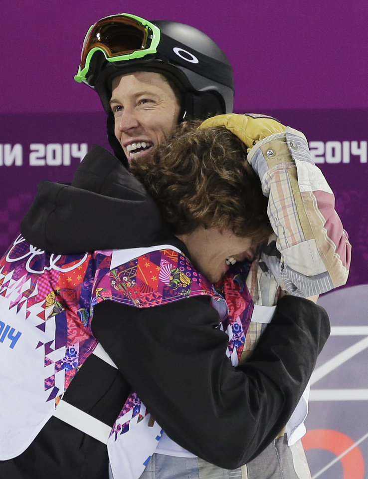 Photo - Switzerland's Iouri Podladtchikov, bottom, celebrates with Shaun White of the United States after Podladtchikov won the gold medal in the men's snowboard halfpipe final at the Rosa Khutor Extreme Park, at the 2014 Winter Olympics, Tuesday, Feb. 11, 2014, in Krasnaya Polyana, Russia. (AP Photo/Andy Wong)