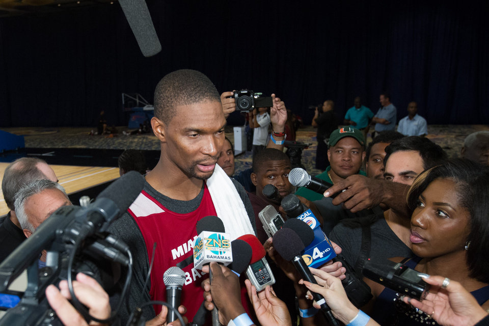 Photo - Miami Heat forward Chris Bosh is interviewed during a break from a training camp session at the Atlantis Resort in Paradise Island, Bahamas, Tuesday, Oct. 1, 2013. The two-time defending NBA champions opened training camp Tuesday at the resort, with two practices scheduled for opening day. (AP Photo/Bahamas Visual Services, Dante Carrer)