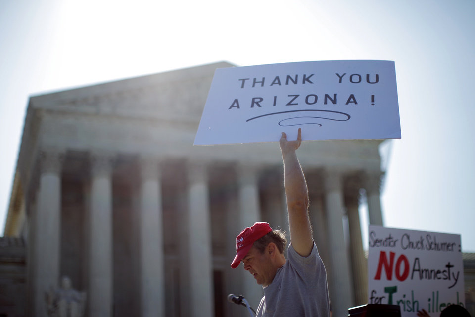 "A supporter of Arizona's ""show me your papers"" immigration law, who declined to be identified, demonstrates in front of the Supreme Court in Washington, Wednesday, April 25, 2012. (AP Photo/Charles Dharapak) ORG XMIT: DCCD101"
