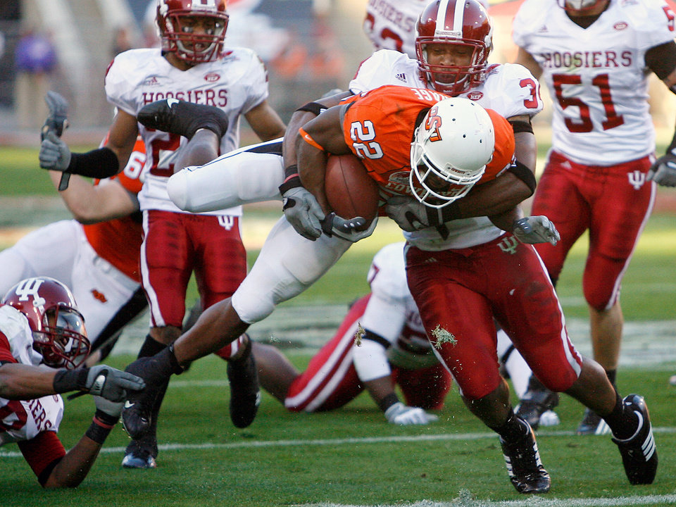 Photo - Oklahoma State's Dantrell Savage (22) is hit by Indiana's Will Patterson (34) as Savage scores a touchdown during the Insight Bowl college football game between Oklahoma State University (OSU) and the Indiana University Hoosiers (IU) at Sun Devil Stadium on Monday, Dec. 31, 2007, in Tempe, Ariz. 