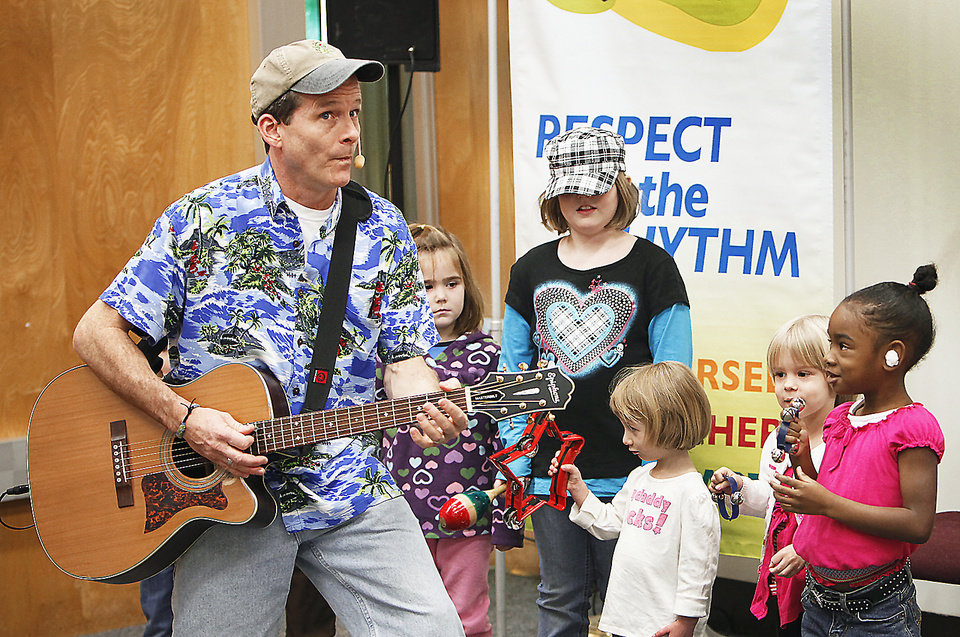 Photo - Award-winning children's entertainer Jim Cosgrove, known as Mr. Stinky Feet, plays guitar and sings Tuesday  at Warr Acres Library.  PHOTOS BY DAVID MCDANIEL, THE OKLAHOMAN