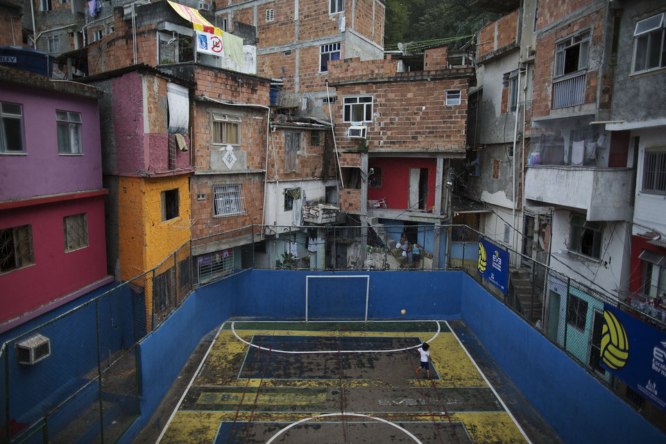 Photo - In this April 27, 2014 photo, a boy plays alone as he practices scoring in a small court in the Tavares Bastos shantytown in Rio de Janeiro, Brazil. The high costs of preparing for the 2013 Confederations Cup and upcoming World Cup, blamed in part by the late rush to get projects done, ignited a wave of public criticism from a population already tired of poor public services and widespread corruption, yet in Brazil, soccer is a unifying force. (AP Photo/Leo Correa)