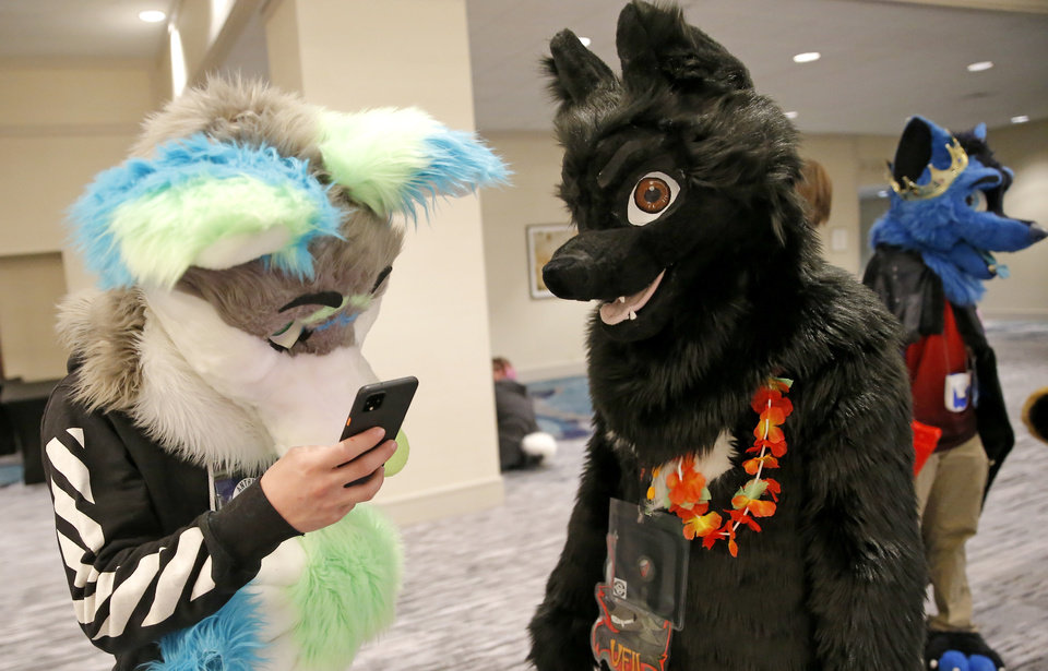 Photo - Aspen looks at his phone next to Veil at the AnthroExpo 2020 at the Sheraton Oklahoma City Downtown Hotel, Friday, Jan. 31, 2020.  [Sarah Phipps/The Oklahoman]