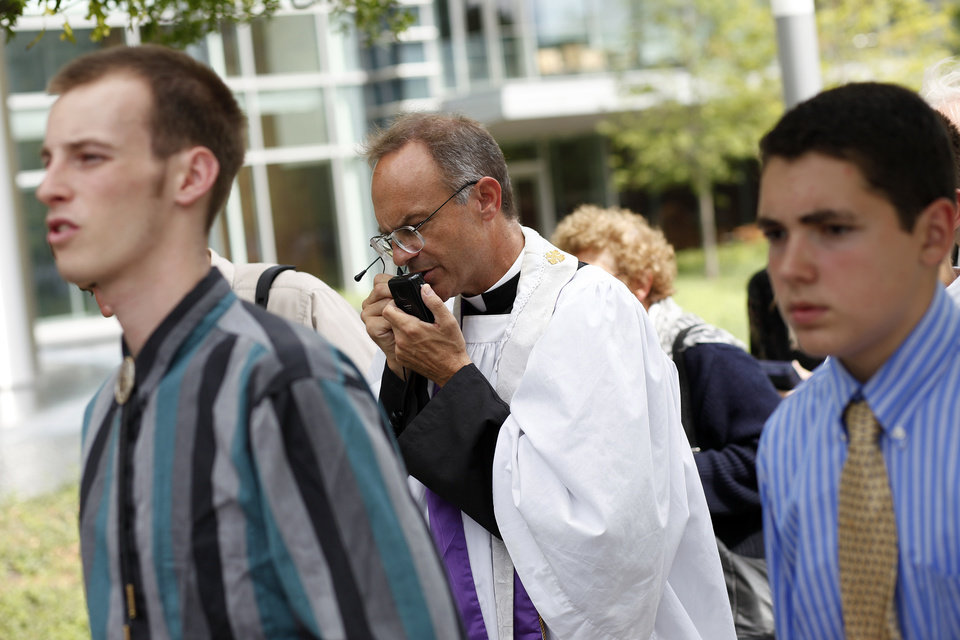Photo - Father Kenneth Novak, of St. Marys Kansas, leads a rosary procession in downtown Oklahoma City in protest of the Black Mass, Sunday, Sept. 21, 2014.  Photo by Garett Fisbeck, For The Oklahoman