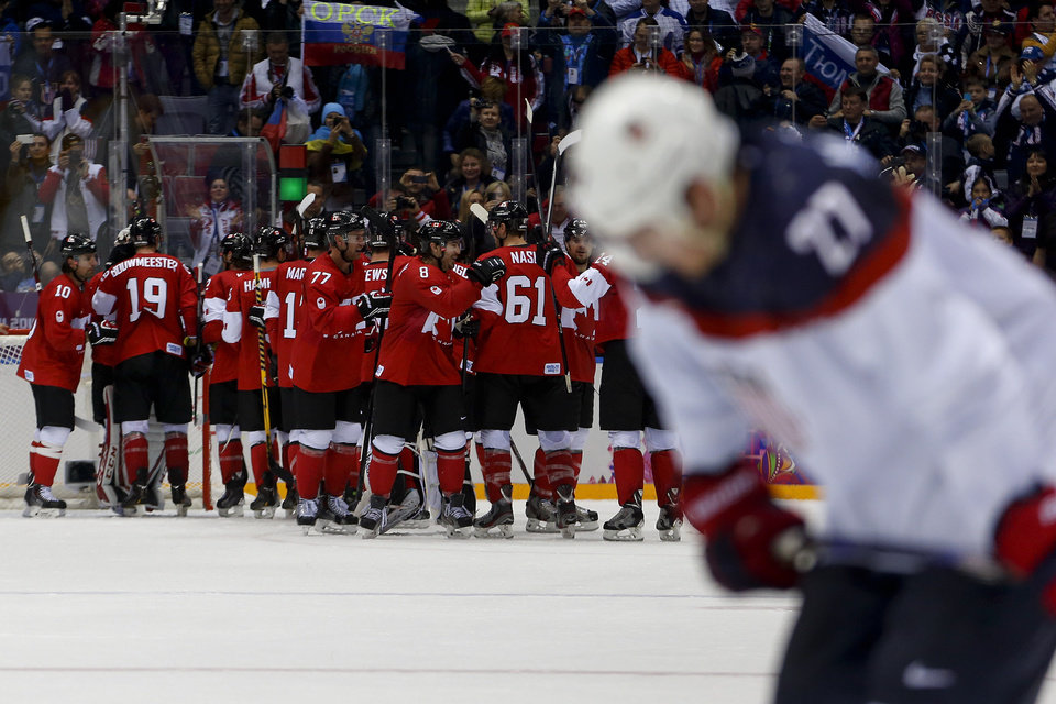 Photo - Team Canada celebrates after beating the USA 1-0 in a men's semifinal ice hockey game at the 2014 Winter Olympics, Friday, Feb. 21, 2014, in Sochi, Russia. (AP Photo/Petr David Josek)