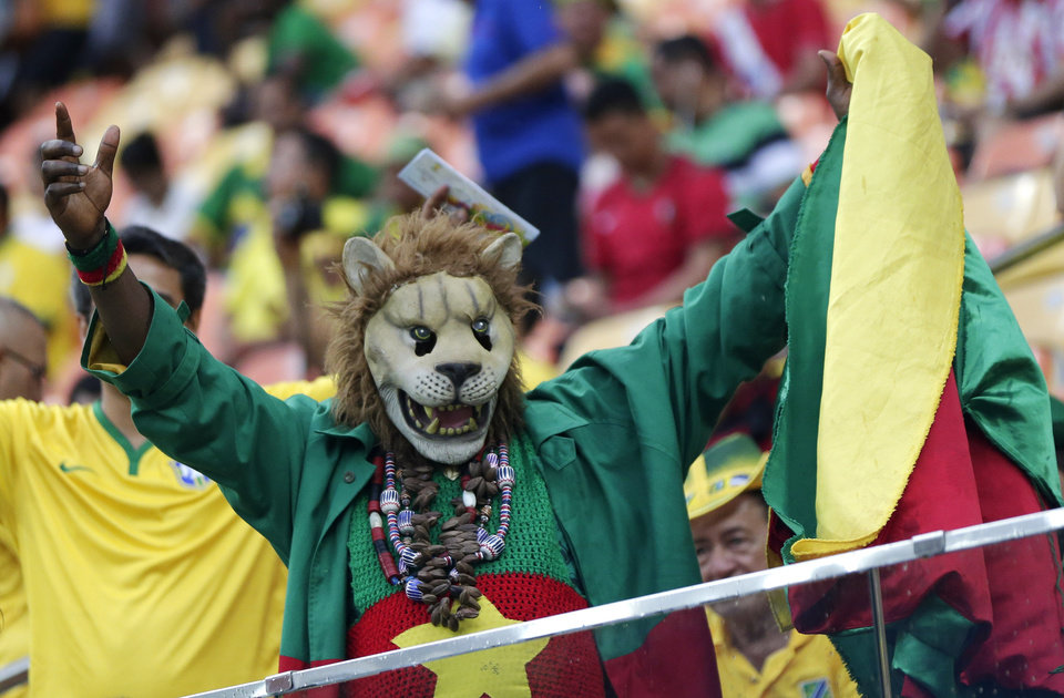 Photo - A Cameroon fan cheers before the group A World Cup soccer match between Cameroon and Croatia at the Arena da Amazonia in Manaus, Brazil, Wednesday, June 18, 2014.  (AP Photo/Marcio Jose Sanchez)