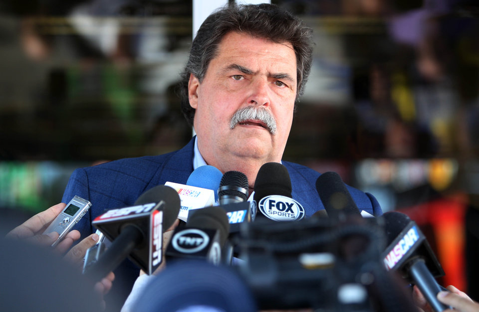 Photo - NASCAR President Mike Helton speaks outside the NASCAR hauler at New Hampshire Motor Speedway, Friday, July 11, 2014, in Loudon, N.H. Helton said there is no animosity from the governing body toward the recently formed, nine-team Race Team Alliance that will collaborate on initiatives and issues facing auto racing.  (AP Photo/Jim Cole)