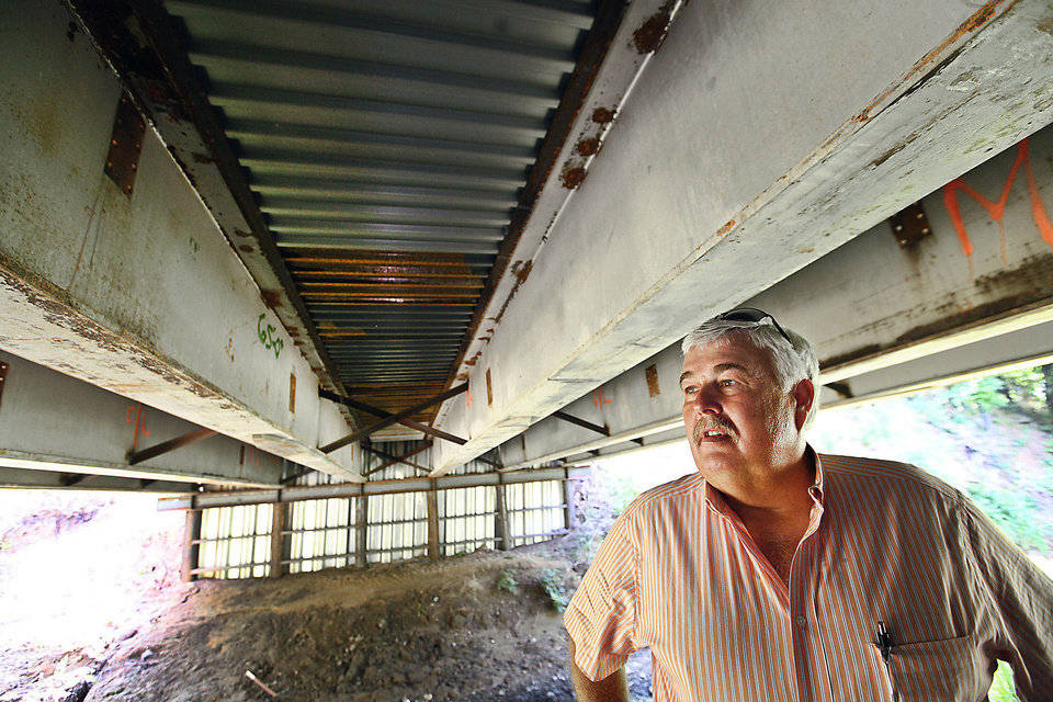 Photo - McClain County Commissioner Wilson Lyles under a bridge near Washington, Oklahoma, built using steel beams from the old Interstate 40 Crosstown, Wednesday, July 10, 2013.  Photo by David McDaniel, The Oklahoman