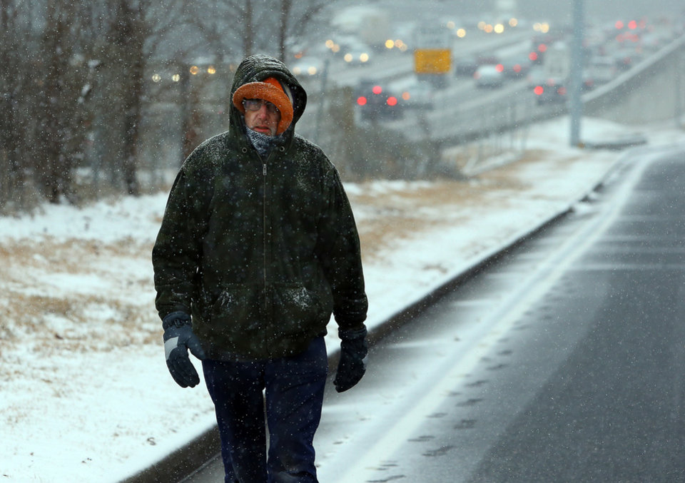 Photo - Dedicated employee David Gress, 47, walks along Peachtree Industrial Boulevard making a 6-mile trip on foot to work from his home in Dunwoody on Tuesday, Jan. 28, 2014, in Doraville, Georgia.   (AP Photo/Atlanta Journal-Constitution, Curtis Compton)