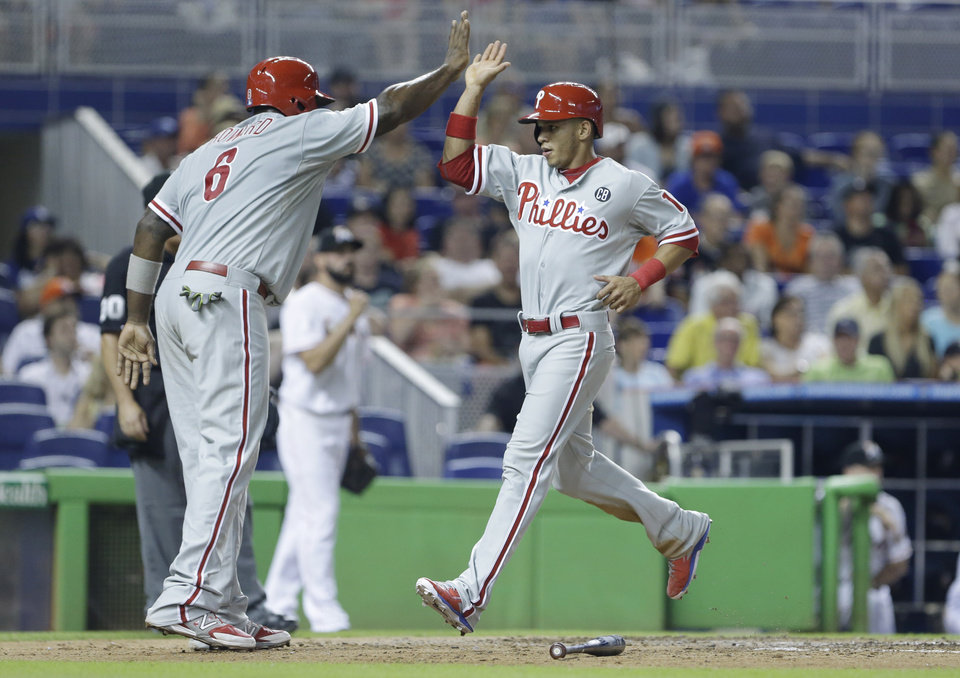 Photo - Philadelphia Phillies' Ryan Howard, left, celebrates with Cesar Hernandez after Cameron Rupp (not shown) hit a double, scoring Howard and Hernandez during the sixth inning of a baseball game against the Miami Marlins, Thursday, July 3, 2014 in Miami. (AP Photo/Wilfredo Lee)
