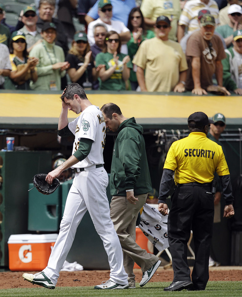Photo -   Oakland Athletics pitcher Brandon McCarthy (32) leaves the field with a trainer after being hit in the head by a ball hit by Los Angeles Angels' Erick Aybar in the fourth inning of a baseball game, Wednesday, Sept. 5, 2012, in Oakland, Calif. (AP Photo/Ben Margot)