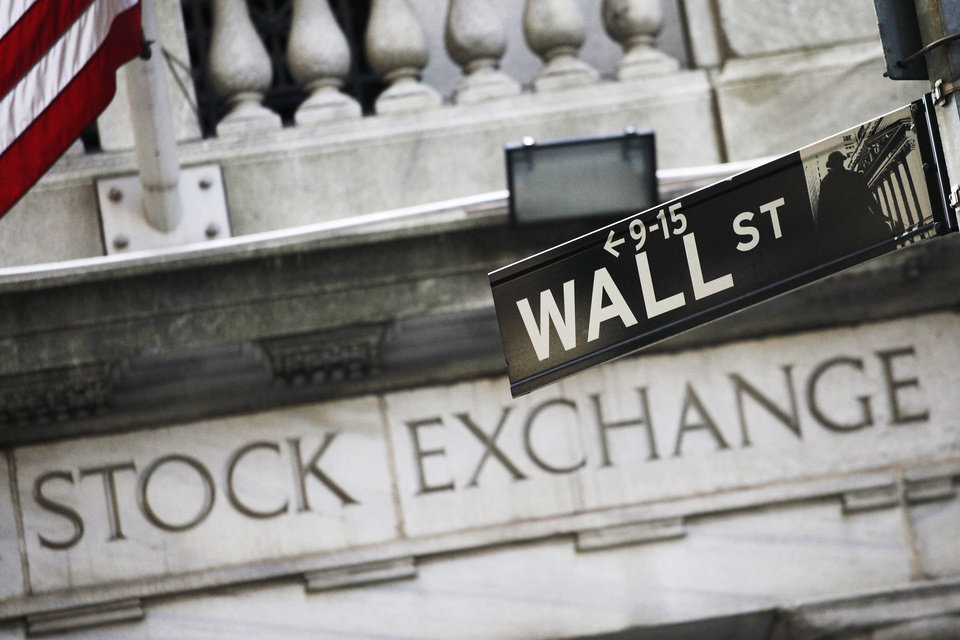 Photo - FILE - This July 16, 2013 file photo shows a street sign for Wall Street outside the New York Stock Exchange in New York. World stocks were muted as investors awaited an update on the U.S. economy later Wednesday June 18, 2014 from the Federal Reserve following its two-day policy meeting, while Japanese markets rose on a weaker yen.   (AP Photo/Mark Lennihan, File)