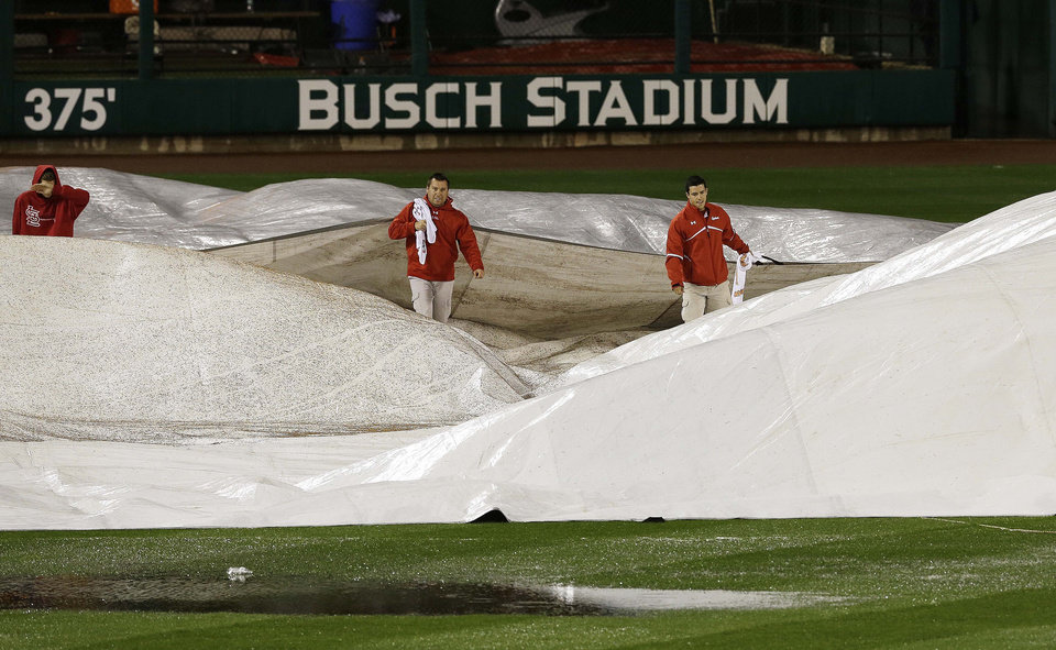 Photo -   Ground crew prepares the field during the rain delay of Game 3 of baseball's National League championship series between the St. Louis Cardinals and the San Francisco Giants, Wednesday, Oct. 17, 2012, in St. Louis. (AP Photo/Patrick Semansky)