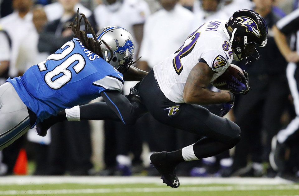 Photo - Baltimore Ravens wide receiver Torrey Smith (82) is stopped by Detroit Lions free safety Louis Delmas (26) during the second quarter of an NFL football game in Detroit, Monday, Dec. 16, 2013. (AP Photo/Rick Osentoski)