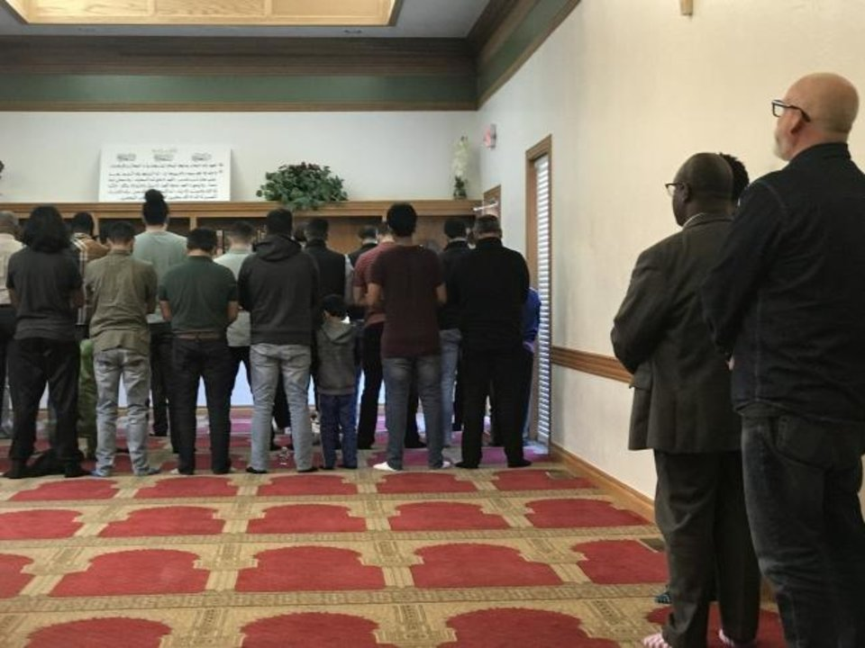 Photo -  Non-Muslims, at right, watch as Muslims pray at the Islamic Society of Greater Oklahoma City's mosque, 3815 N St. Clair Ave. [Carla Hinton/The Oklahoman]