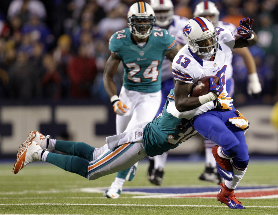 Photo -   Buffalo Bills wide receiver Stevie Johnson (13) is tackled by Miami Dolphins strong safety Chris Clemons (30) during the first half of an NFL football game on Thursday, Nov. 15, 2012, in Orchard Park, N.Y. (AP Photo/Gary Wiepert)