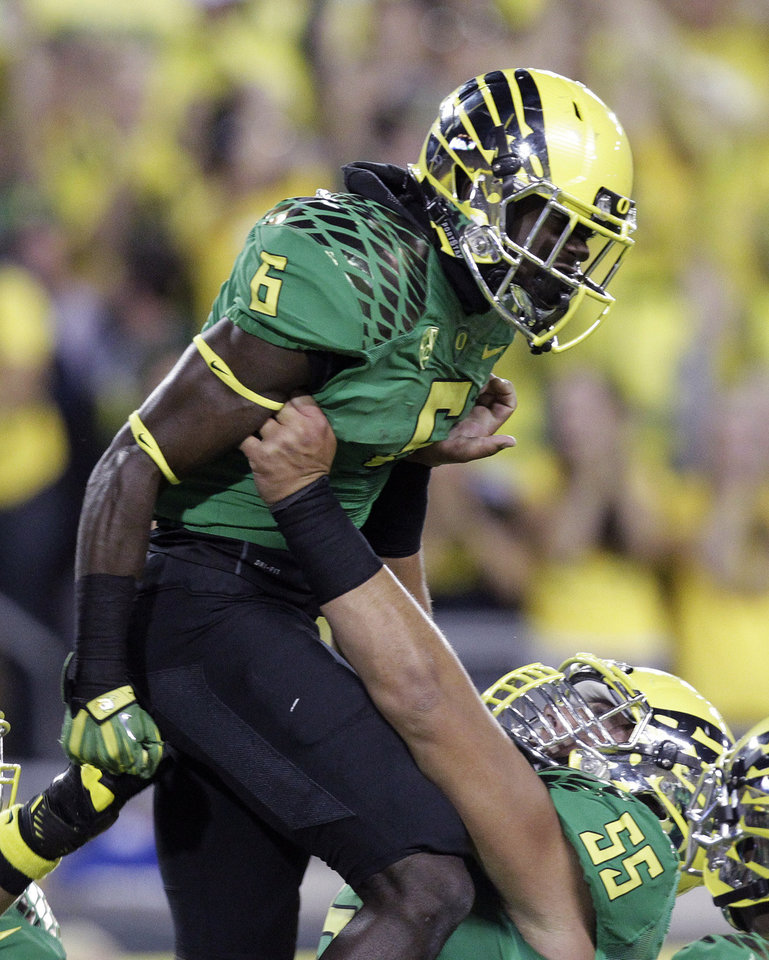 Oregon running back De'Anthony Thomas, left, celebrates his touchdown with offensive lineman Hroniss Grasu during the first half of an NCAA college football game against Washington in Eugene, Ore., Saturday, Oct. 6, 2012.(AP Photo/Don Ryan)
