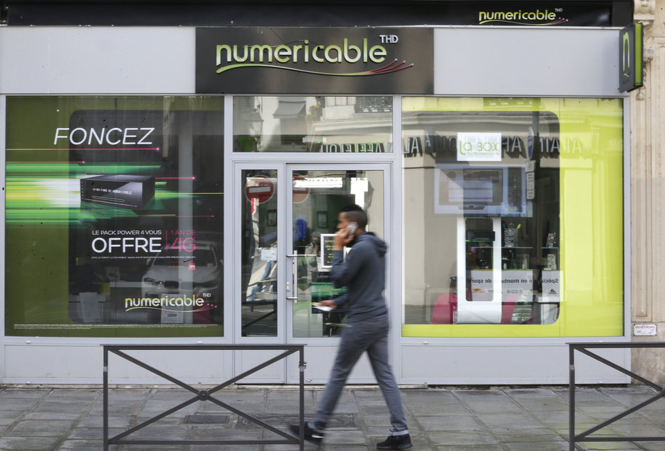 Photo - A man uses his phone as he walks past a Numericable shop in Paris, Tuesday March 18, 2014. France's Vivendi has decided to start exclusive negotiations with media company Altice, the holding company for Numericable, over the possible sale of its unit SFR, France's No. 2 mobile phone operator. The move is a blow for Bouygues, a conglomerate that had made a competing offer and raised it to 11.3 billion euros ($15.8 billion) this week. (AP Photo/Jacques Brinon)