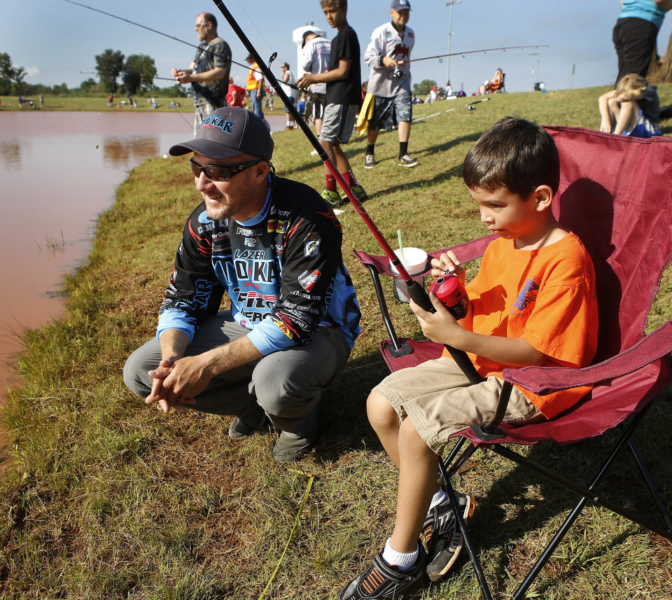2012 Bassmaster Angler of the Year Brent Chapman, from Lake Quivira, KS, shares advice with 6 year-old angler Tristan Perez of Moore. Moore hosted its annual kids fishing derby Saturday morning, July 27, 2013,  at Buck Thomas Park.  As part of the event this year, a charity called the Tackle the Storm Foundation handed out rods and reels to tornado victims. Several bass fishing pros from Oklahoma attended the event to help distribute the fishing equipment and share fishing tips with the young anglers. An event official  said about 250 children participated in the fishing derby. Photo  by Jim Beckel, The Oklahoman.