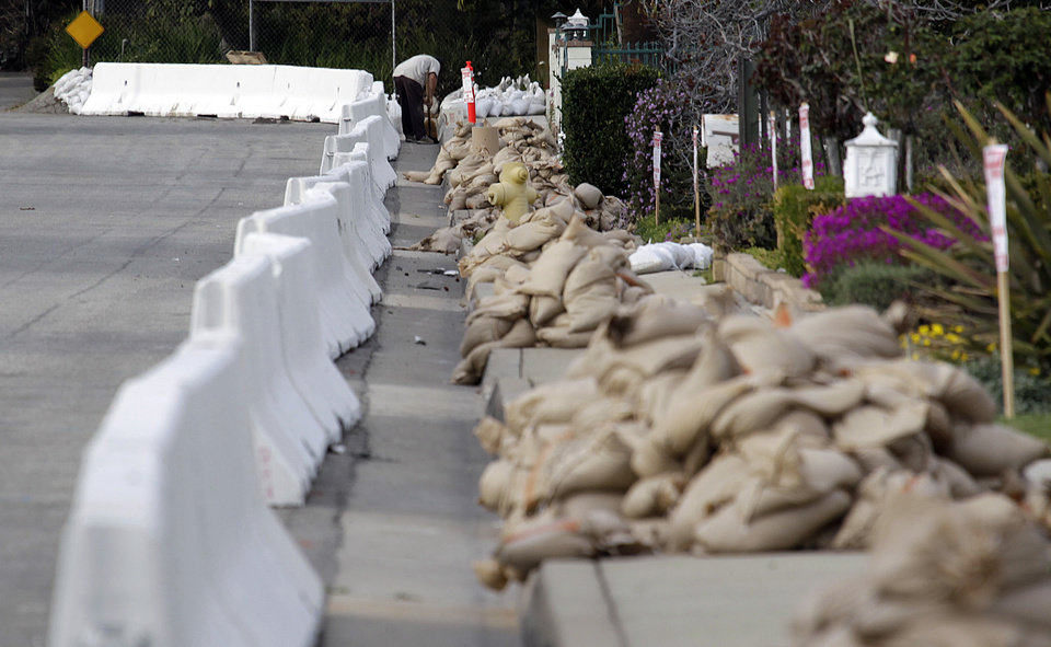 Photo - A man places sandbags at the top of a street lined with K-rail and sandbags in Glendora, Calif., as the city and residents prepare for possible flooding Thursday, Feb. 27, 2014. Mandatory evacuation orders have been issued for 1,000 homes in two foothill suburbs east of Los Angeles in advance of a powerful storm. The cities of Glendora and Azusa issued the orders at midday Thursday for homes that could be endangered by debris flows from nearly 2,000 acres (810 hectares) of steep mountain slopes burned by a wildfire last month. For days, both cities have been making extensive preparations including sandbagging. California received widespread rain Wednesday and early Thursday from the first of two back-to-back storms. The more powerful second storm is due overnight.  (AP Photo/Reed Saxon)