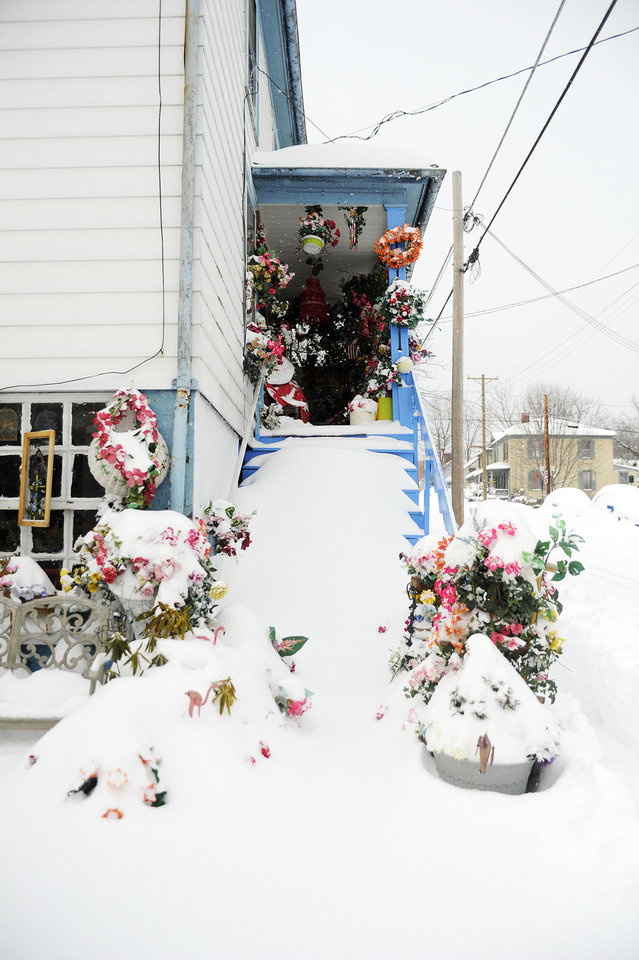 Photo - Snow covers the flowers of a porch along Beverley Street after a snowstorm accumulating over a foot of snow fell on Thursday, Feb. 13, 2014, in Staunton, Va. (AP Photo/The News Leader, Katie Currid)