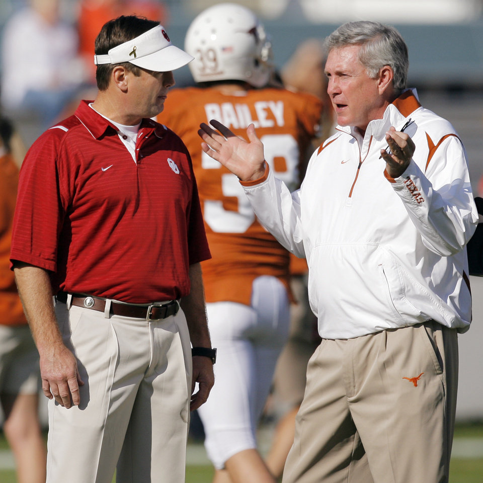Photo - OU head coach Bob Stoops, left, and Texas head coach Mack Brown talk before the Red River Rivalry college football game between the University of Oklahoma Sooners (OU) and the University of Texas Longhorns (UT) at the Cotton Bowl in Dallas, Texas, Saturday, Oct. 17, 2009. Photo by Nate Billings, The Oklahoman