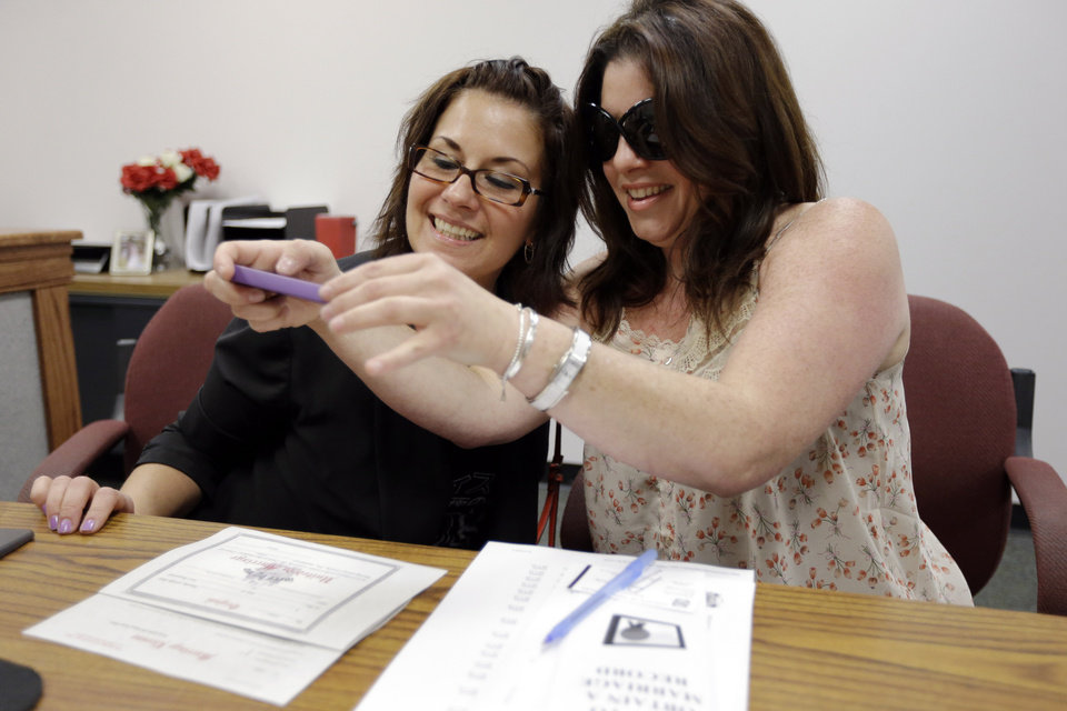 Tamara Davis, left, and Nicola Cucinotta snap a photograph of their marriage license they obtained at a Montgomery County office despite a state law banning such unions, Wednesday, July 24, 2013, in Norristown, Pa.  Five same-sex couples have obtained marriage licenses in the suburban Philadelphia county that is defying a state ban on such unions.   (AP Photo/Matt Rourke)