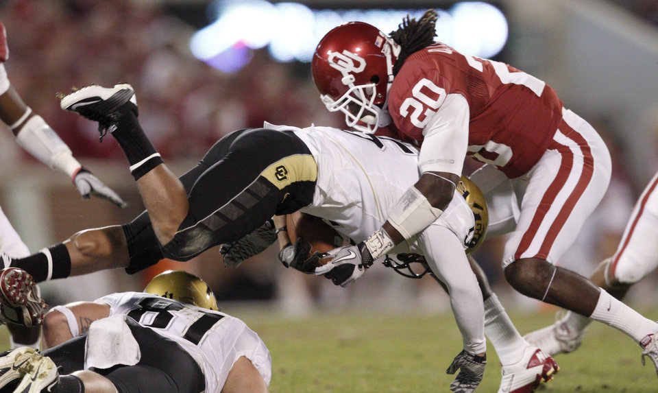 Photo - OU's Quinton Carter brings down Colorado's Rodney Stewart during the college football game between the University of Oklahoma (OU) Sooners and the University of Colorado Buffaloes at Gaylord Family-Oklahoma Memorial Stadium in Norman, Okla., Saturday, October 30, 2010. Photo by Bryan Terry, The Oklahoman