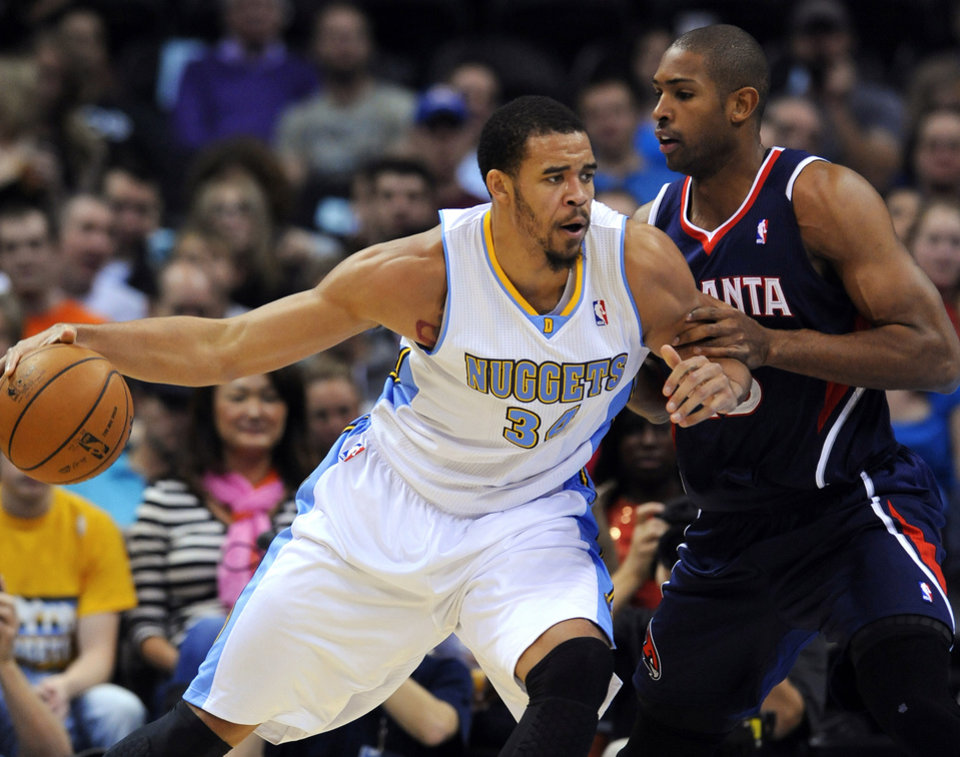 Photo - Denver Nuggets center JaVale McGee (34) bumps Atlanta Hawks center Al Horford, right, from the Dominican Republic during the first quarter of an NBA basketball game Thursday, Nov. 7, 2013, in Denver. (AP Photo/Jack Dempsey)