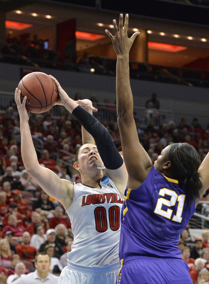 Photo - Louisville's Sara Hammond (00) is fouled from behind while attempting to shoot over the defense of LSU's Shanece McKinney (21) during the second half in a regional semifinal game at the NCAA women's college basketball tournament, Sunday, March 30, 2014, in Louisville, Ky. Louisville defeated LSU 73-47. (AP Photo/Timothy D. Easley)