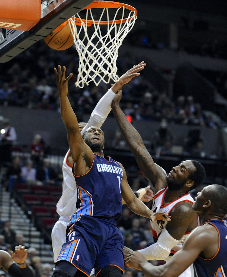 Photo - Charlotte Bobcats' Kemba Walker (15) shoots against Portland Trail Blazers' LaMarcus Aldridge, rear, and JJ Hickson, right, during the first half of an NBA  basketball game in Portland, Ore., Monday, March 4, 2013. (AP Photo/Greg Wahl-Stephens)
