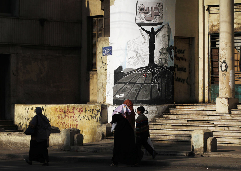 Photo - A woman walks past a residential building with graffiti and Arabic, top center, that reads,