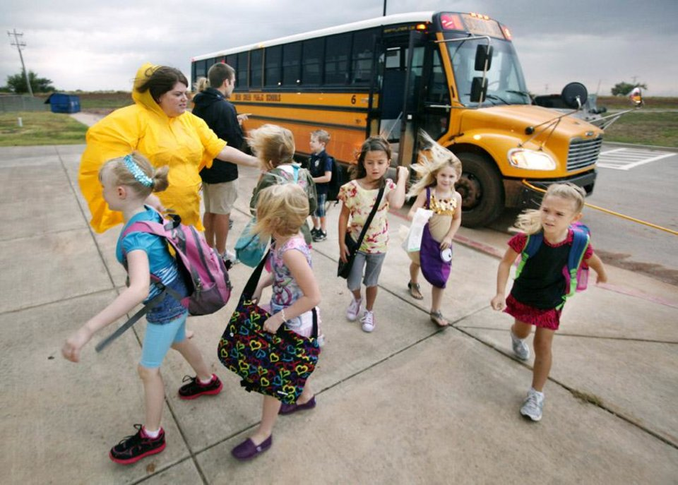 Photo -  Music teacher Amy Thomas greets students arriving by bus as a thunderstorm moves through on the first day of school at Rose Union Elementary in the Deer Creek School District in Oklahoma City Thursday, Aug. 11, 2011. Photo by Paul B. Southerland, The Oklahoman ORG XMIT: KOD