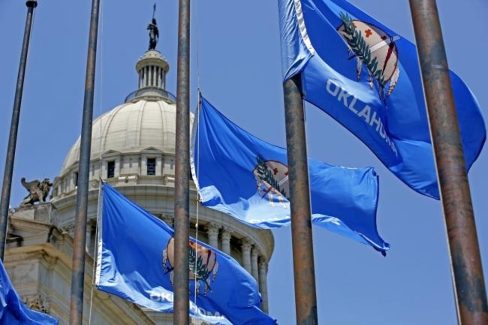 Photo -  Oklahoma flags fly at half staff at the state Capitol in Oklahoma City. [THE OKLAHOMAN ARCHIVES]