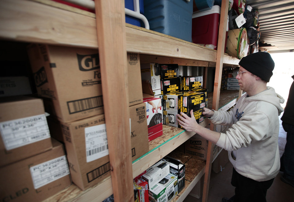 Photo - Pastor Brian Hastings,  of the Memorial Baptist Church in Fond du Lac,Wis., sorts some supplies in a storage building Wednesday at the Emmanuel Baptist Church in McLoud.  David McDaniel - The Oklahoman