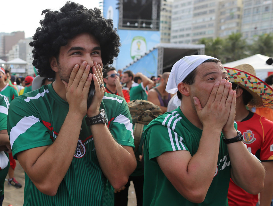 Photo - Mexico soccer fans react after a second goal was scored against their team as they watch the World Cup round of 16 match against Netherlands on a live telecast inside the FIFA Fan Fest area on Copacabana beach in Rio de Janeiro, Brazil, Sunday, June 29, 2014. The Netherlands staged a dramatic late comeback, scoring two goals in the dying minutes to beat Mexico 2-1 and advance to the World Cup quarterfinals. (AP Photo/Leo Correa)
