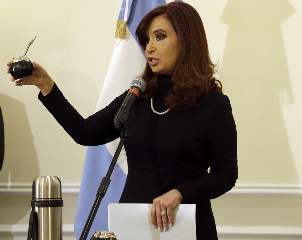 Photo - Argentine President Cristina Fernandez shows a mate gourd, during a news conference in Rome, Monday, March 18, 2013. Pope Francis' diplomatic skills were put to the test Monday as he had lunch with Argentine President Cristina Fernandez: As leader of Argentina's Catholics, he had accused her populist government of demagoguery while she called his position on gay adoptions reminiscent of the Middle Ages and the Inquisition. That was then. On Monday, Fernandez gave the new pope a mate gourd and straw, to hold the traditional Argentine tea that Francis loves, and he gave her a kiss. (AP Photo/Gregorio Borgia)