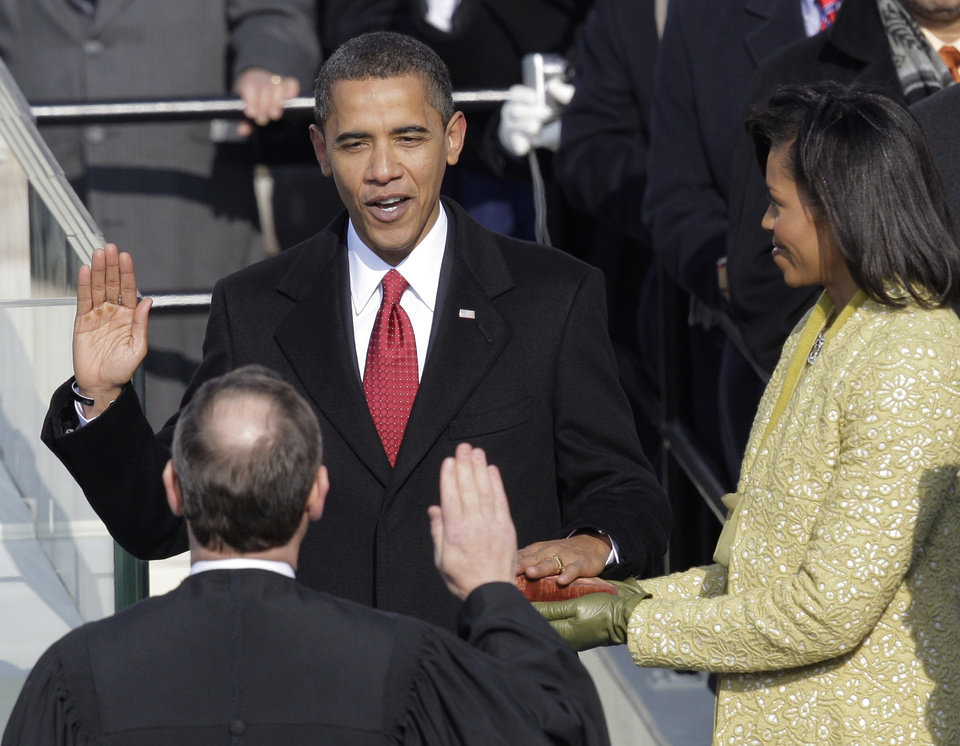 Photo - Barack Obama, left, joined by his wife Michelle, takes the oath of office from Chief Justice John Roberts to become the 44th president of the United States at the U.S. Capitol in Washington, Tuesday, Jan. 20, 2009.  (AP Photo/Jae C. Hong)