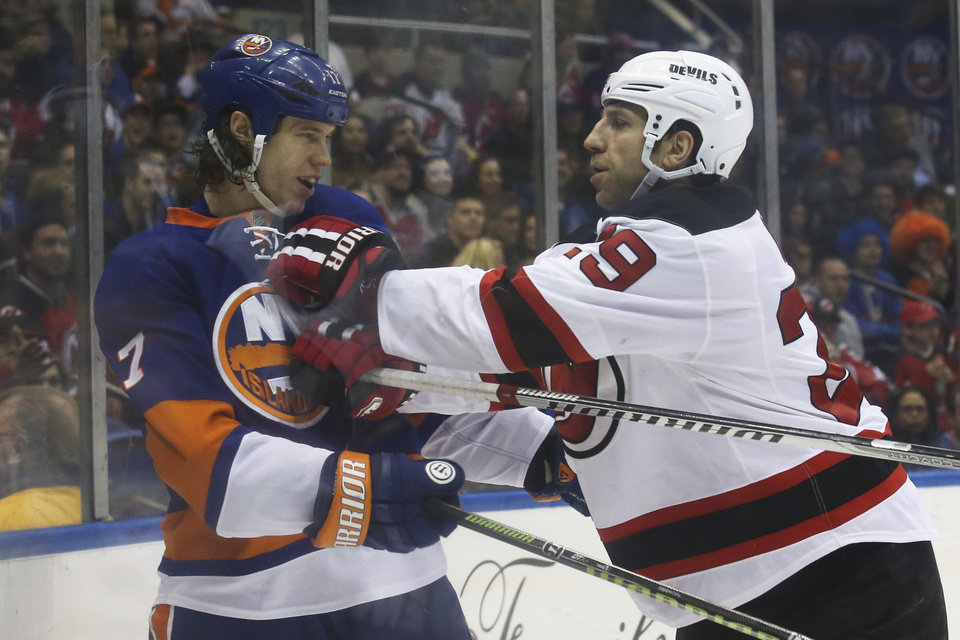 Photo - New York Islanders left wing Matt Martin (17) and New Jersey Devils left wing Ryane Clowe (29) scuffle in the second period of an NHL hockey game on Saturday, March 29, 2014, in Uniondale, N.Y. (AP Photo/John Minchillo)