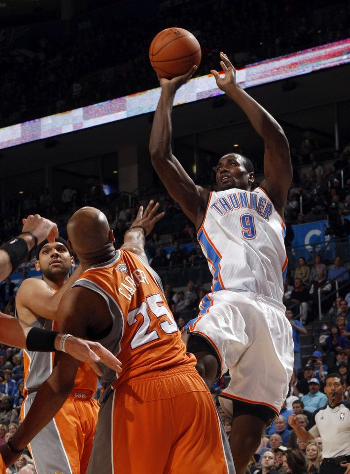 Oklahoma City's Serge Ibaka (9) shoots as Phoenix's Grant Hill (33) and Phoenix's Vince Carter (25) defend during the NBA game between the Oklahoma City Thunder and the Phoenix Suns, Sunday, March 6, 2011, the Oklahoma City Arena. Photo by Sarah Phipps, The Oklahoman.