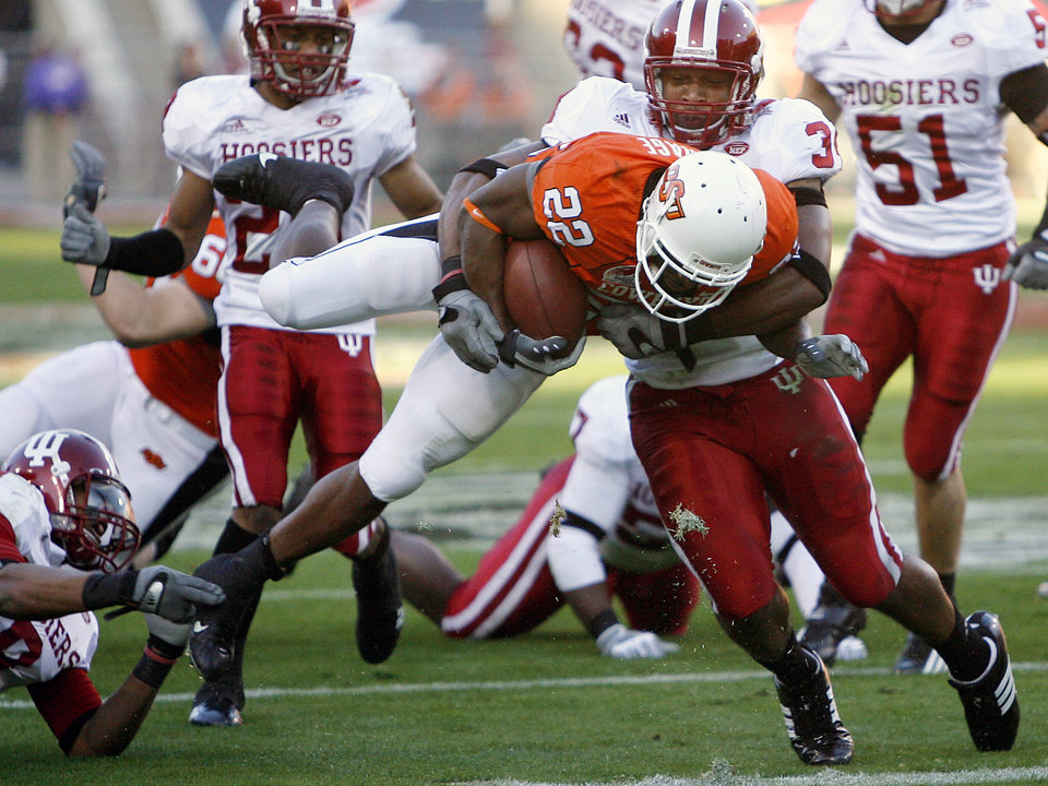 Photo - Oklahoma State's Dantrell Savage (22) is hit by Indiana's Will Patterson (34) as Savage falls just short of a touchdown during the Insight Bowl college football game between Oklahoma State University (OSU) and the Indiana University Hoosiers (IU) at Sun Devil Stadium on Monday, Dec. 31, 2007, in Tempe, Ariz.   BY BRYAN TERRY, THE OKLAHOMAN ORG XMIT: KOD